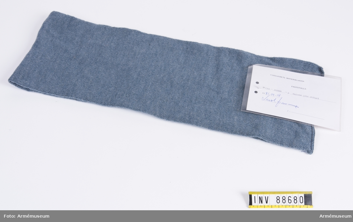"""Stålgrå halsduk av ylle. Vidhängande modellapp med text: """"Försvarets materielverk. Fastställs. M 7345-202000-4 Halsduk ylle stålgrå 1985-09-18. (oläslig underskrift)."""""""