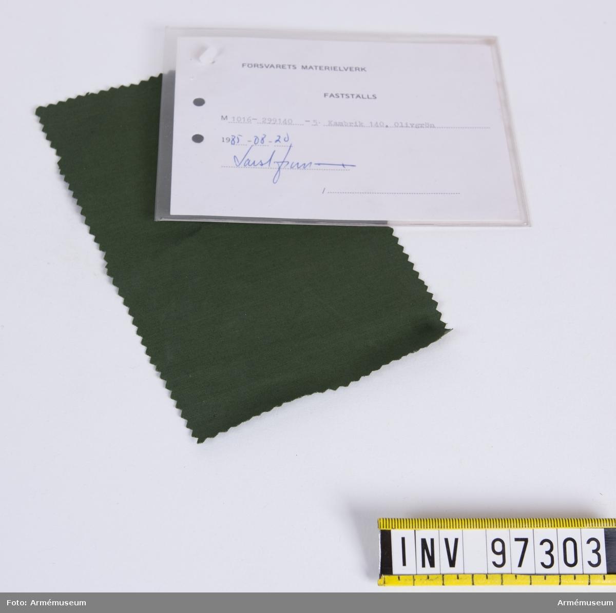 """Vidhängande modellapp med text: """"Försvarets materielverk. Fastställs. M 1016-299140-5. Kambrik 140, Olivgrön. 1985-08-20  (oläslig sign)"""""""
