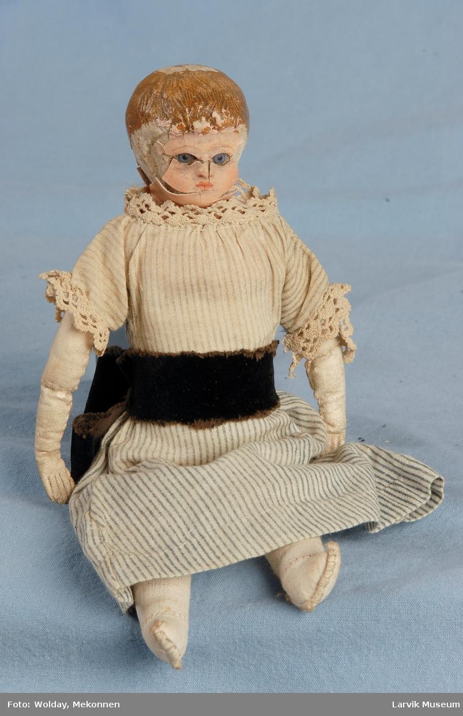 Form: Hode i voks over komposisjon, glassøyne, kropp i tekstil, underarmer i skinn.