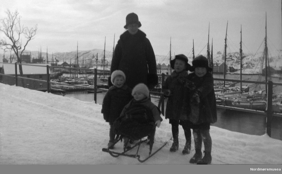 Foto av en kvinne ute med fire små barn med spark. Datering er usikker men trolig rundt 1917-1920. Bildet ser ut til å være fotografert langs Kranaveien i Vågen på Kirkelandet i Kristiansund. Fra Nordmøre museums fotosamlinger.