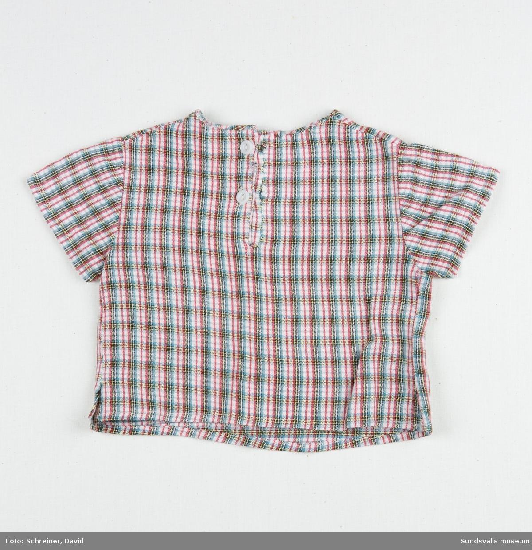 En kortärmad smårutig pojkskjorta med rundad hals som knäpps med två vita plastknappar i ryggen.