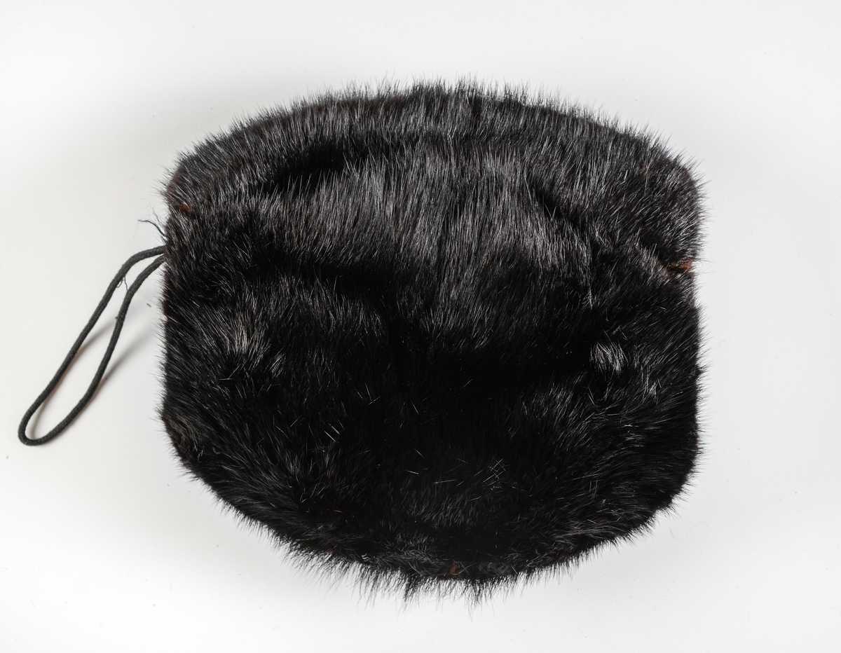 Muffe i svart skinn, fóra med svart silketøy.