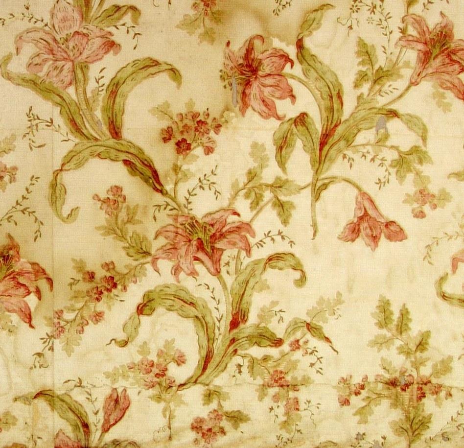 Ett fritt växande mönster med liljor. Tryck i flera rosa och gulgröna nyanser på en cremevit bakgrund.