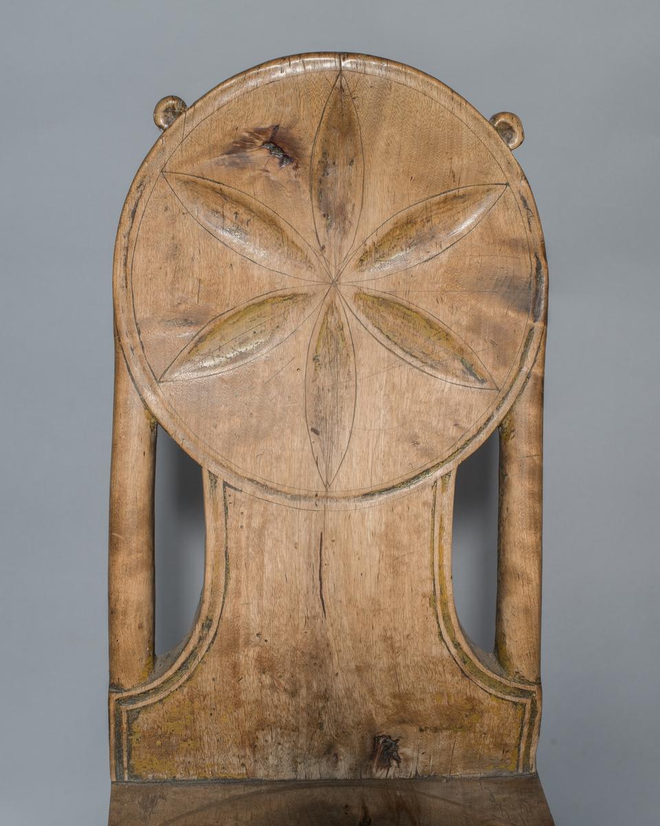 Stol av trä med tre runda intappade ben, lätt utställda. Bakbenet delvis avfasat. Rund sits, med utskjutande bakre parti. Delvis ryggstolpar. Ryggbricka med utskuren dekor, övre delen cirkelrund. Rester av gul färg på sitsens undersida och i ryggbrickans utskärningar.