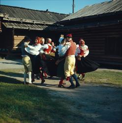 Ett folkdanslag dansar på Moragårdens gårdsplan.