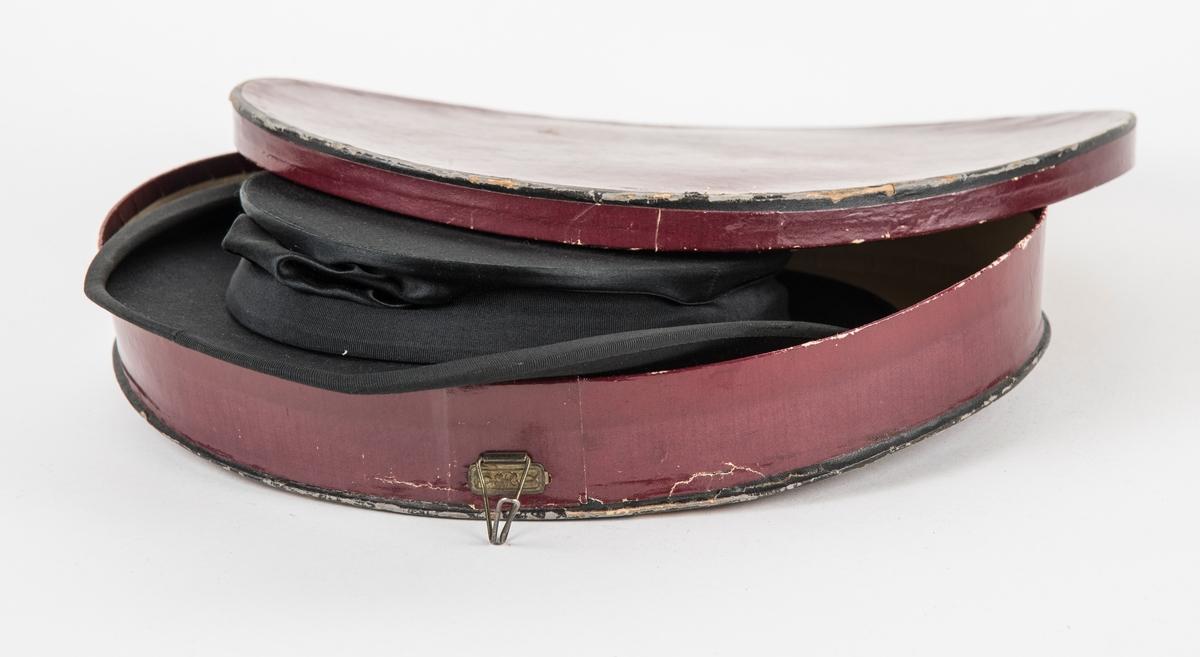 Hatt, A,  høg svart flosshat i blankt silkeliknande stoff.  Ripsband rundt pullen og bremkanten. Fóra med svart silke. Sammanleggbar.  B, Plommeraudt pappetui med metallhandtak og krokar.