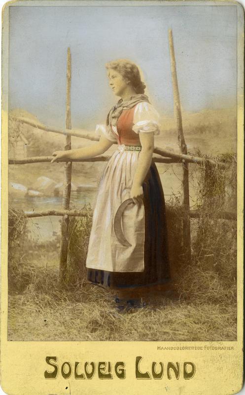 Kolorert studiofotografi av kvinne med sigd og høyhesje. 1906.
