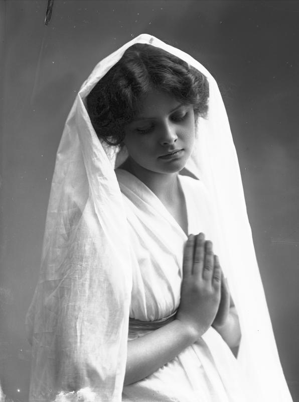 Studioportrett av kvinne i kostyme - hvit kjortel og hvitt slør, som holder hendene foldet. 1908. (Foto/Photo)