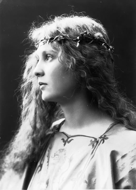 Studioportrett av kvinne i kostyme og utslått hår - overdel med riksvåpen og blomsterkrans i håret. 1908. (Foto/Photo)