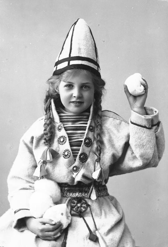 Pike i sameliknende drakt med kofte, lue og belte. I hendene holder hun juksesnøballer. 1908.