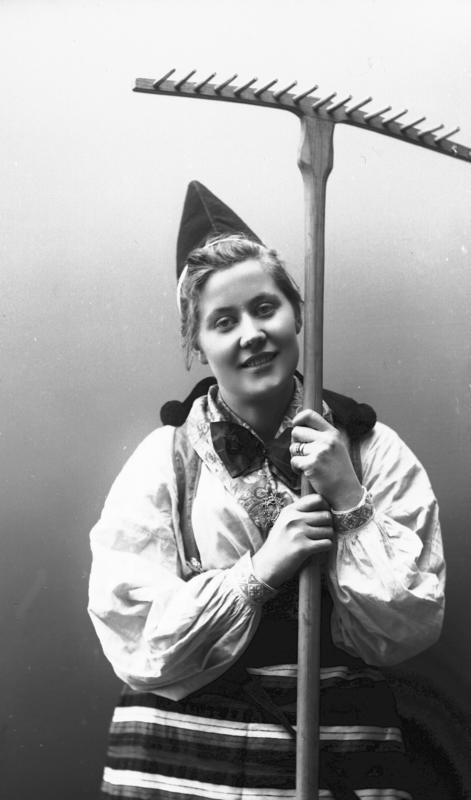 Kvinne i drakt og lue, som holder rive. 1908.