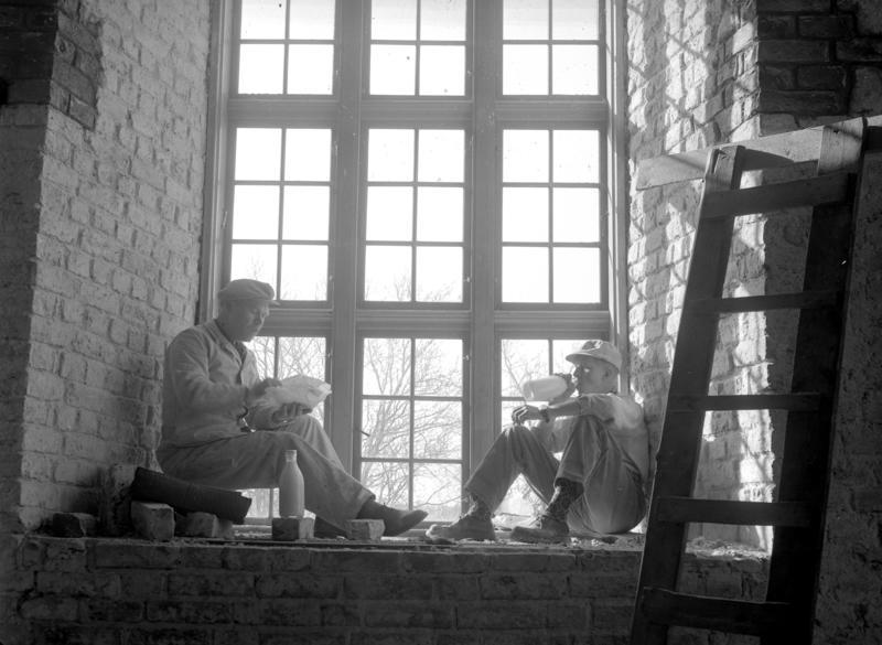Håndverkere lunsj i vinduskarm i Akershus Slottskirke, Oslo, 07.04.1954.
