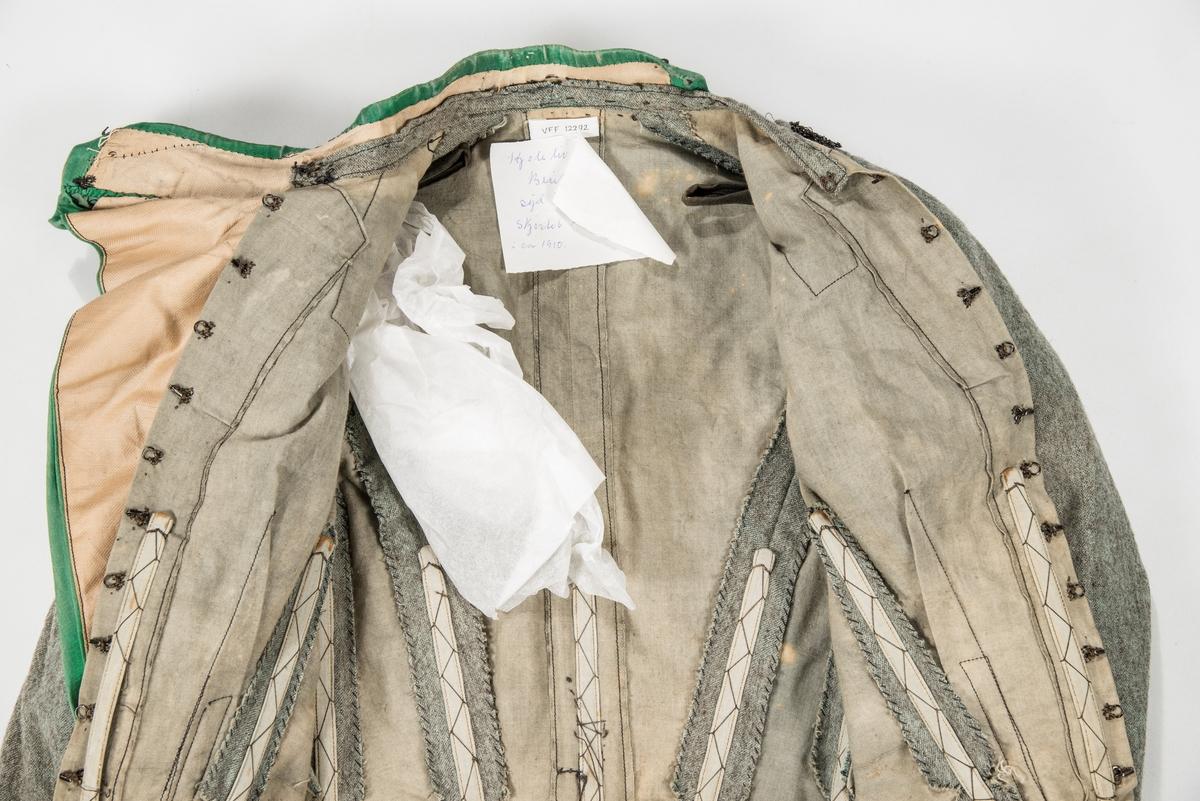 """Kjoleliv i lysegrønt og grått melert ulltøy, bringesmekke og rett krage i grønn silke. Opning midt framme med hekter og krokar. To legg framme og svinga saumar bak.  Todelt erme med legg øverst, og smal nede, liten splitt.  Svart """"perlebord"""" på kvar side på framstykket og rundt ermane. Kjolelivet er fóra med bomullstøy. 9 spilar."""