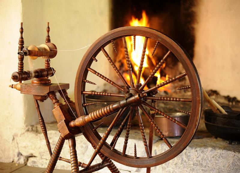 En gammel rokk til å spinne garn på står foran en åpen peis hvor det brenner lunt. (Foto/Photo)