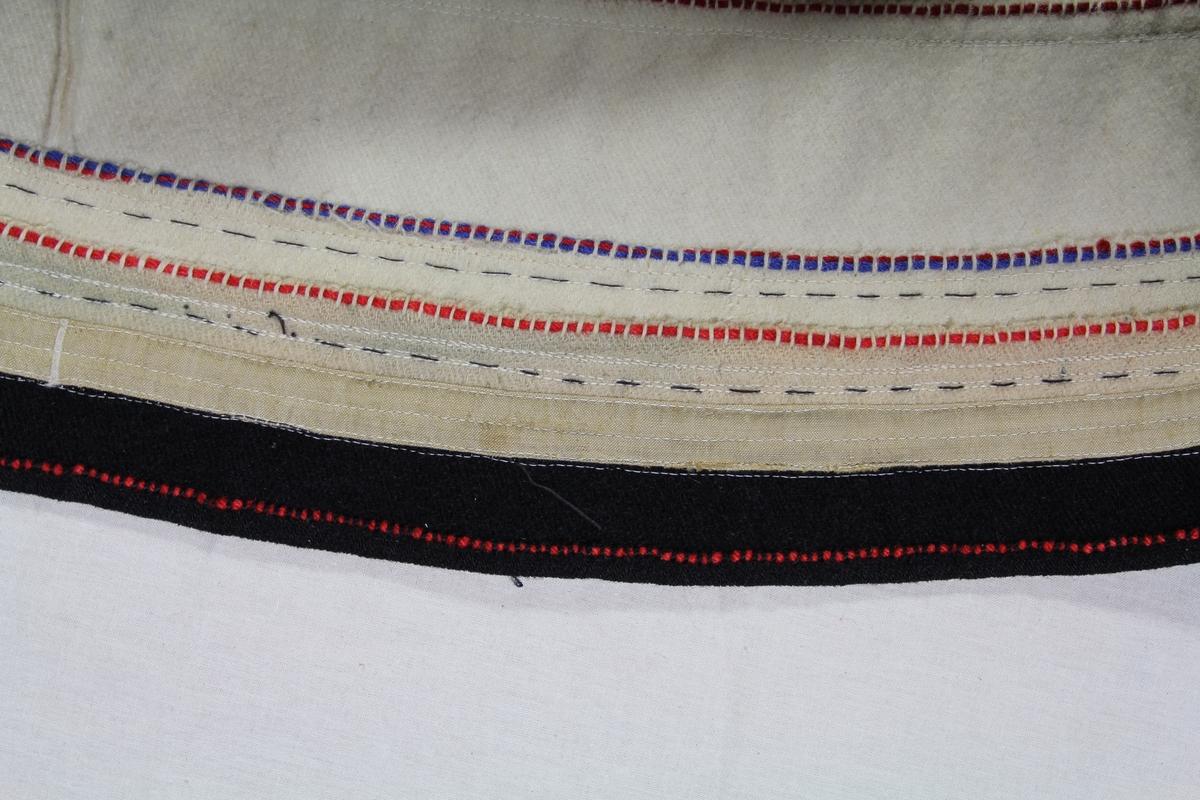 """Stakk til folkedrakt fra Setesdal. I hvit og sort vadmel, sort klede og grønt stoff, broderi i ullgarn. Stakken har rektangulære fangbredder og fem bakbredder. Nedenom tre kantinger """"skorer"""". Den nederste av sort vadmel, de to andre som er av hvit vadmel er på retten av sort stoffremse festet ved sin øvre kant. På vrangen er det midtre skoren langs overkanten prydet med en line av rød ullråd, den øverste med line av rødt og blått. Sort linning hvis frontpart er prydet med grønn kanting og brodert rutebord hvis midtrekke dannes av røde kvadrater. I vinklene mellom disse prikkpunkter i vekselvis grønt og grått. På sidene av rutemotivet hvit """"krok"""", røde kontursting og """"takker"""" i rødt og hvitt. På """"upplutstykket"""" er en kant av sort klede og fire sorte loddrette striper. På kantingen er det 10 åttebladsrosetter, et tredelt triangel og nederst """"takkebord"""". Stolpene har samme takkebord og et firebladsmotiv. Sorte seler."""