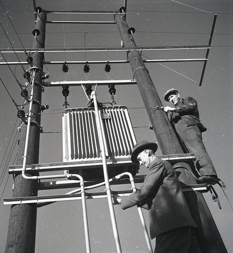 Högt upp på en elstolpe monterar två elektriker kraftledningar som ska leda ström genom Hälsingland. Året är 1951 och ena elektrikern bär som arbetskläder hatt och kavaj medan den andre bär, för ändamålet lämpligare, jacka och keps.