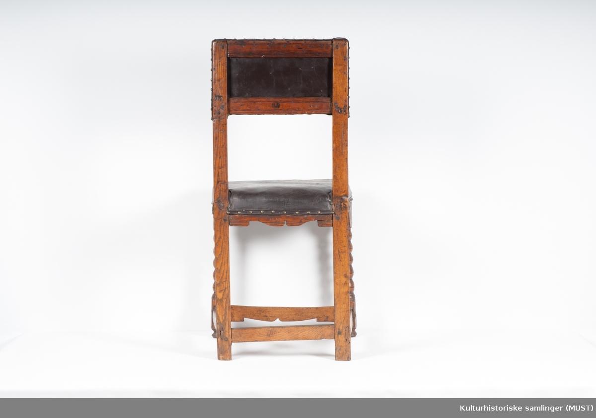 """Rektangulær stoppet rygg. Firkantede akterstaver. Kuledreide forbein.  På baksiden av stolen er det brent inn: """"NB"""" tre steder. Stopping og trekk er sekundært. Profilerte sarger av furu. Den bakre sargen er sveifet i nedre kant. Fremmerste sprosse er av bjørk og sveifet i nederste kant. Toppstykket og tverspross er av furu.  Tilstand: god"""