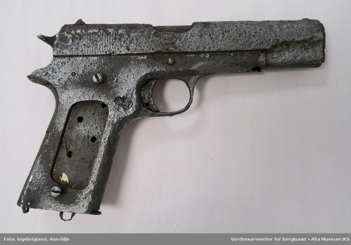 Pistol med vanlig form. Deler av pistolen ser ut til å mangle. Stålet er såpass skadet at det ikke er noe kjennemerke eller serienummer å se. Her og der er det etset hull slik at man ser fjæringen og noe av de andre indre komponentene i pistolen.