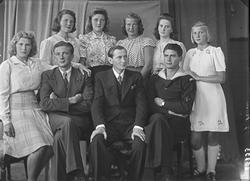 Gruppebilde. Familiegruppe på ni. Tre menn og seks unge kvin