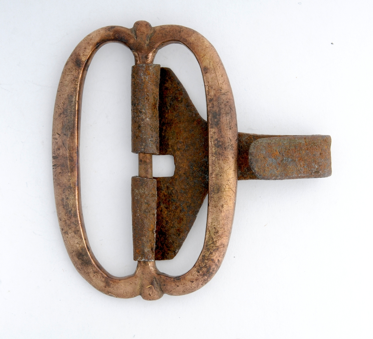 Beltespenne i messing. Oval form, ingen dekor. Stolpen er støypt i eitt med spenna. Kroken smidd i jern rundt stolpen.