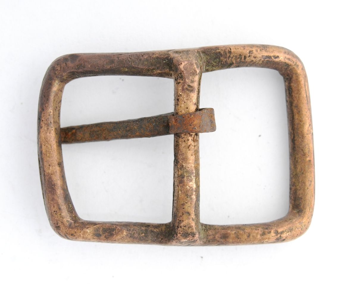 Beltespenne støypt i messing. Rektanguler form, ingen dekor. Tann i jern er smidd rundt stoplen på midten.