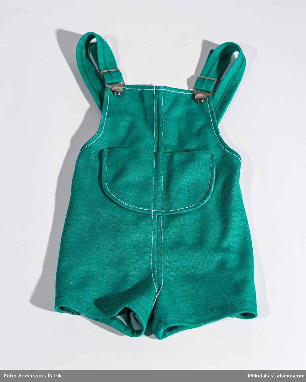 """Kortbyxa med hängslen i storlek 84 från 1975.  Byxan är grön och har en stor ficka framtill på bröstet. I byxan finns en lapp fastsydd med tryckt text: """"danish dressed MADE IN DENMARK"""" och """"HOTEX KONFEKTION 84 SIMBa"""""""