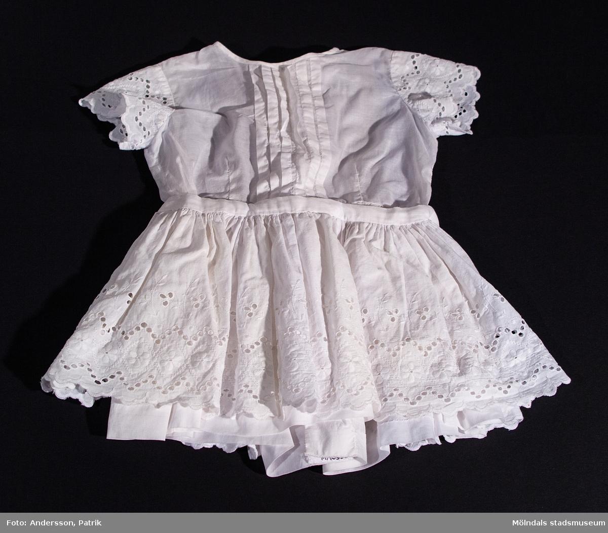 Vit brodyrklänning, från början av 1960-talet. Man knäpper klänningen längs hela ryggen med vita knappar och knyter en rosett i ryggslutet.  Klänningen är hemsydd. Tyget kommer troligtvis från Mölnlycke fabriker i Krokslätt.