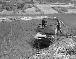 Båter og tømmerbom ved Lomnessjøens vestre bredd, antakelig