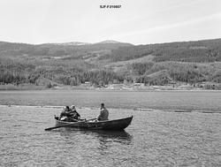 Tre fløtere i en av Glomma fellesfløtingsforenings robåter p