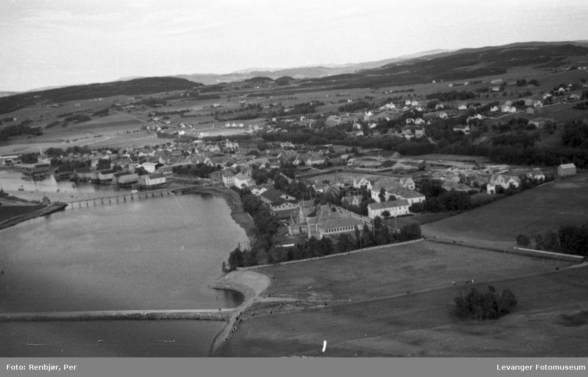 Flyfoto av Levanger, tatt av tenåringen Per Renbjør med sin fars Leica.  Oversikt over byen med Sundbrua og jetèen.