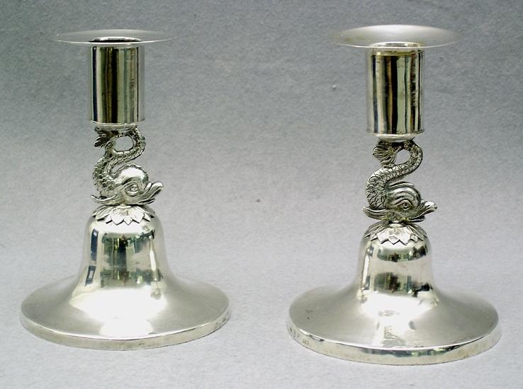 """Enl liggare: """"Ljusstakar, 1 par av silver, ciselerade delfiner sammanbinder ljushållare och foten. Höjd 11,3 cm. Stämplar: M.F. (Magnus Fryberg 1817-1830) - tre kronor - Jönköpings stadsstämpel - M3 (1818)"""""""