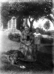 Agnes Johansson med pojke och hund i trädgården, Skinnarbo,