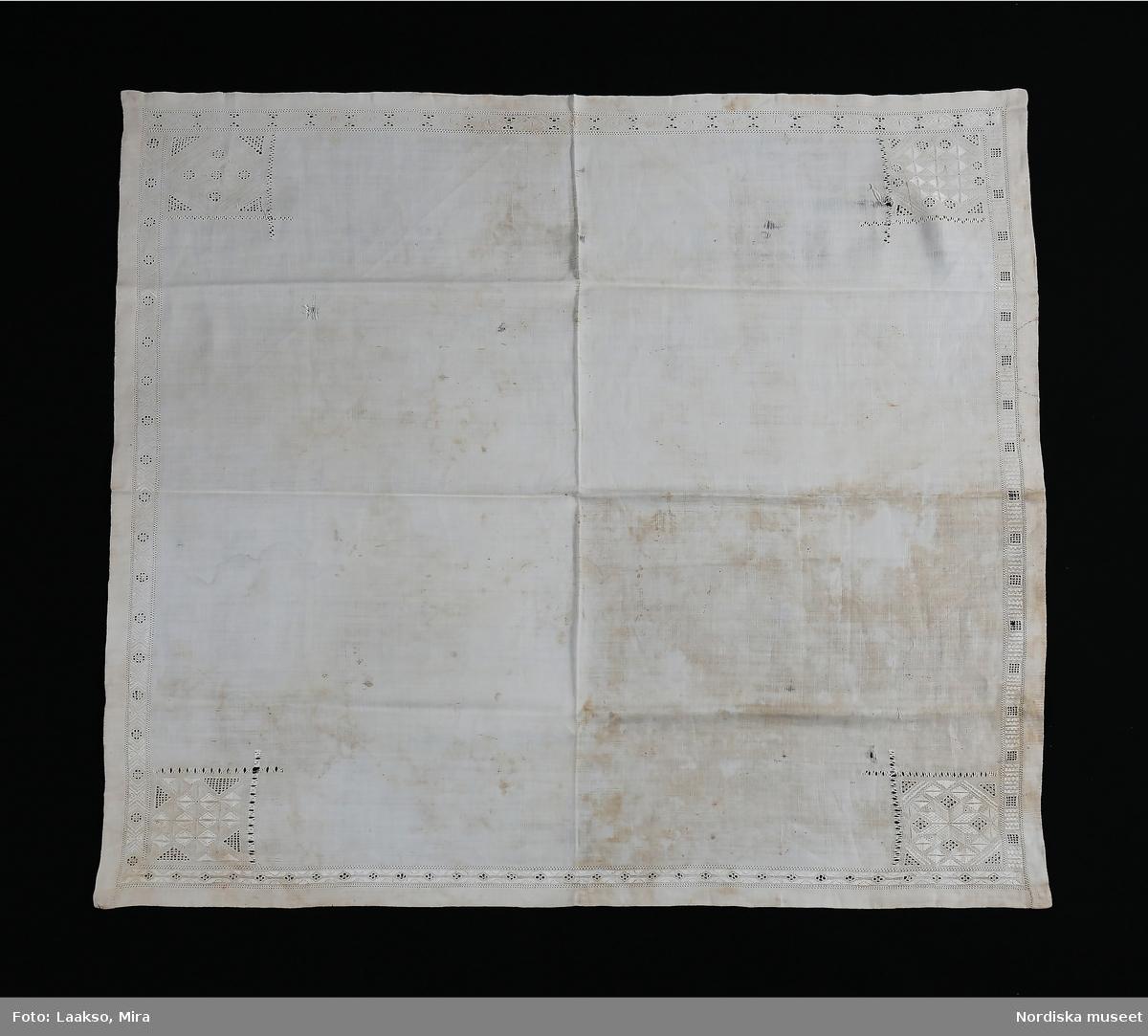Kvadratiskt kläde av handvävd linnelärft, 2 cm breda fållar runtom, kantbård 2 cm bred i rätlinjig plattsöm och utskårssöm med dubbla rader enkel utdragssöm  längs med bården. Varje sida har ett eget mönster. I hörnen kvadratiska broderier i vitt lingarn 10 x 10 cm i samma tekniker. Olika mönster i alla hörnen. På avigan finns i varje hörn en tränsad hank för att fästa en dinglande lapp oftast broderad och kantad med spets. Själva handklädet kan också ha varit kantat med en spets. Denna typ av linnekläde från södra Småland hör till samma dräktområde som Skåne och Blekinge där liknande kläden använts till högtidsdräkten som handkläde och vid kyrkbesök som bokkläde kring psalmbokem. Vid stora kalas har det även kunnat användas som förningsduk kring medförda varor.  Vid begravningar har det även kunnat bäras som huvudduk. /Berit Eldvik 2010-06-30