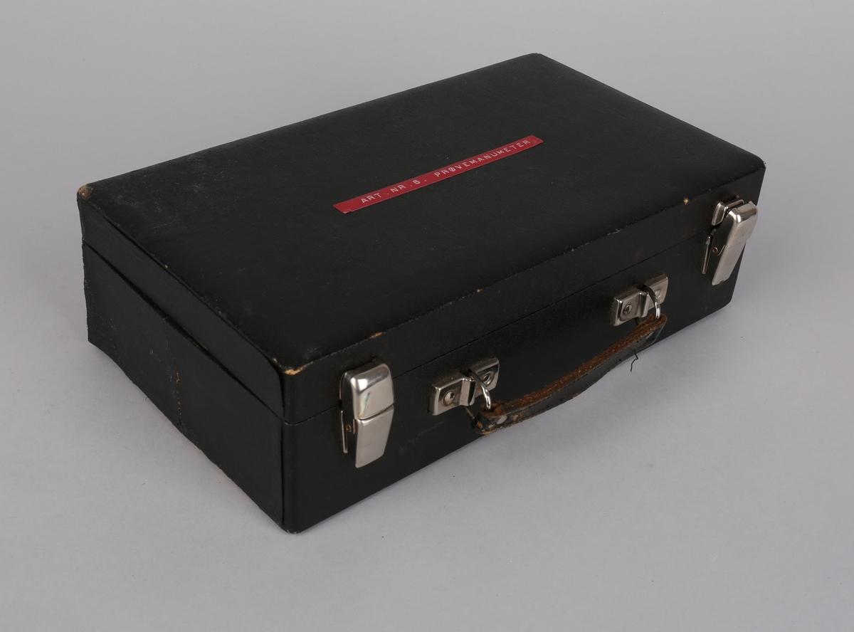 Prøvemanometer i skinnskrin med løse deler samt dokumenter.