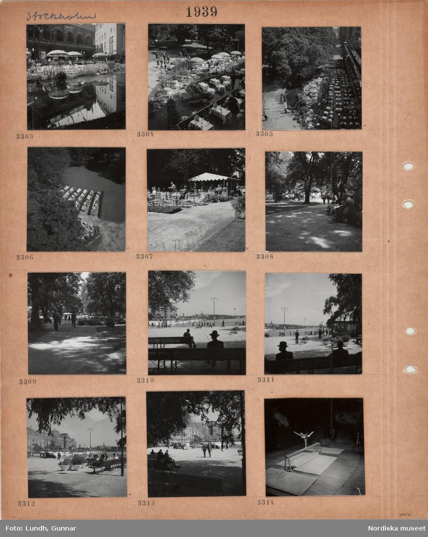 Motiv: Stockholm, Berns uteservering i Berzelii park, bord, parasoller, damm med växter, gångväg, parkbänkar, mindre uteservering med kiosk, träd, Nybroviken med skärgårdsbåtar vid kaj, i bakgrunden Nordiska museet, kvinnlig gymnast på bom.