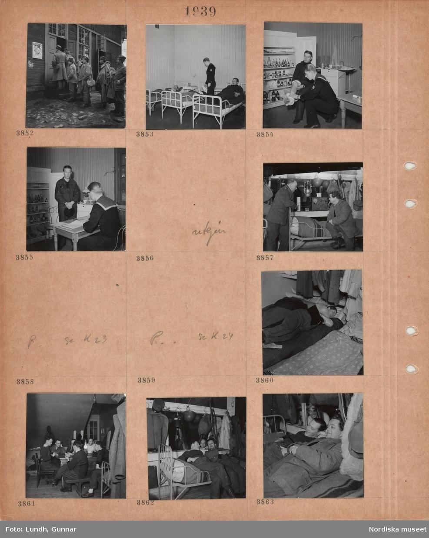 Motiv: Män i militära kläder, män står i kö utanför en träbyggnad, tre män ligger i enkla vita sängar, en man i matroskläder står bredvid, en man sitter framför ett skåp fullt med flaskor och burkar och får ena foten omlagd av en man i matroskläder, man i matroskläder sitter vid ett litet bord med en liggare, en annan man står framför, interiör logement, två män samtalar vid en enkel säng, hjälmar, lykta, päls hänger på krokar på en bjälke, en man ligger påklädd på en madrass på golvet, flera män sitter vid ett bord och spelar kort, två män ligger bakåtlutade över en säng och samtalar,