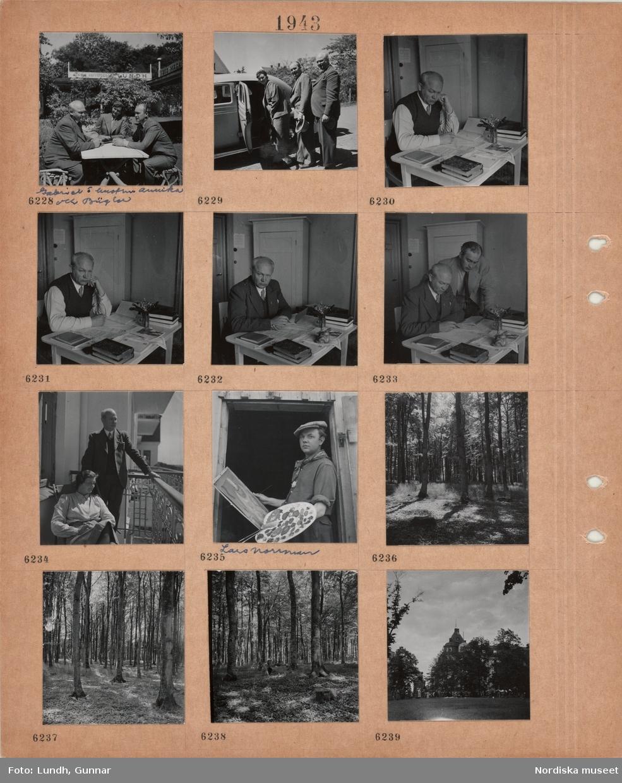 """Motiv: Två män och en kvinna, Gabriel Jönsson o hustrun Annika och Bügler, sitter vid ett trädgårdsbord, i bakgrunden skyltar """"Kungl. Hoffotograf _ Lundh"""", """"FOTO-MAGASIN"""", en kvinna och två män vid en bil med öppen bakdörr, författaren Gabriel Jönsson sitter vid ett litet skrivbord med papper och böcker, vas med liljekonvalj, en man tittar över hans axel, Gabriel Jönsson med hustru på balkong i solsken, konstnären Lars Norrman med palett och målning i händerna, bokskog med silat solljus, en kvinna sitter på huk i skogen, folkmassa i park."""