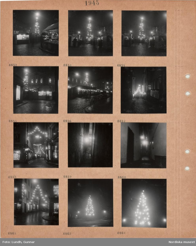 Motiv: Stockholm, Stortorgets julmarknad, salustånd, hög julgran med tänd belysning, stenlagd gata med tända juldekorationer, butiksfönster och skyltar, smal gränd med tänd vägglykta, julgran med tänd belysning.