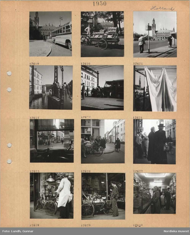 Motiv: Holland, turistbuss framför byggnad med torn, fredspalatset i Haag, en man vid en lång transportcykel lastad med grönsakslådor, väntande personer vid spårvagnshållplats framför fredspalatset, väntande personer och fordon vid broöppning vid kanal, tvätt upphängd på linor, utblick genom restaurangfönster mot gata, gathörn, fotgängare, cyklister, spårvagnsspår, två äldre kvinnor står på en trottoar, parkerade cyklar framför skyltfönster med lampor, man i ljus rock, man i kostym står vid cykel parkerad vid skyltfönster, interiör livsmedelsbutik, köande kunder.