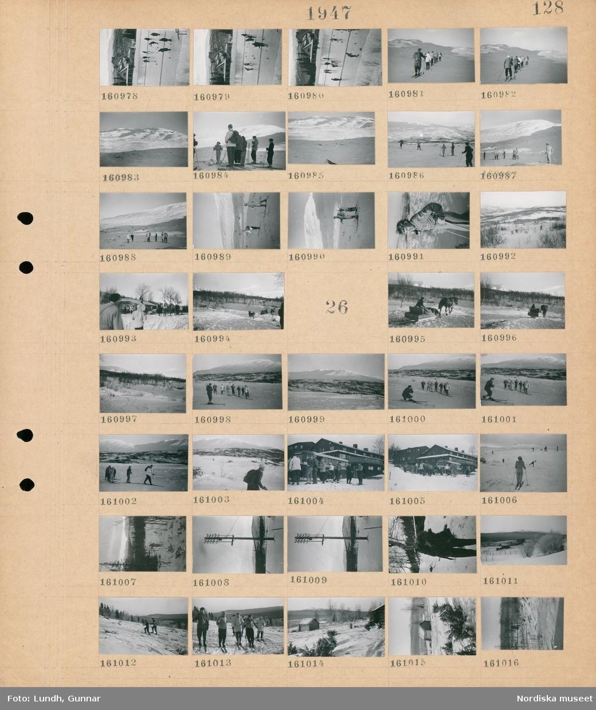 Motiv: (ingen anteckning) ; Människor spelar curling på en curlingbana utomhus, kvinnor och män åker skidor i ett snötäckt landskap med fjäll, snötäckt landskapsvy med fjäll, kvinnor och män med skidor utanför ett hus, en hund.  Motiv: (ingen anteckning) ; En person kör en hästdragen släde i ett snötäckt landskap med skog och fjäll, en man fotograferar en grupp kvinnor och män som åker skidor, en grupp kvinnor och män på skidor vid en buss utanför en byggnad, en telefonstolpe, snötäckt landskapsvy med skog och ett timmrat hus.