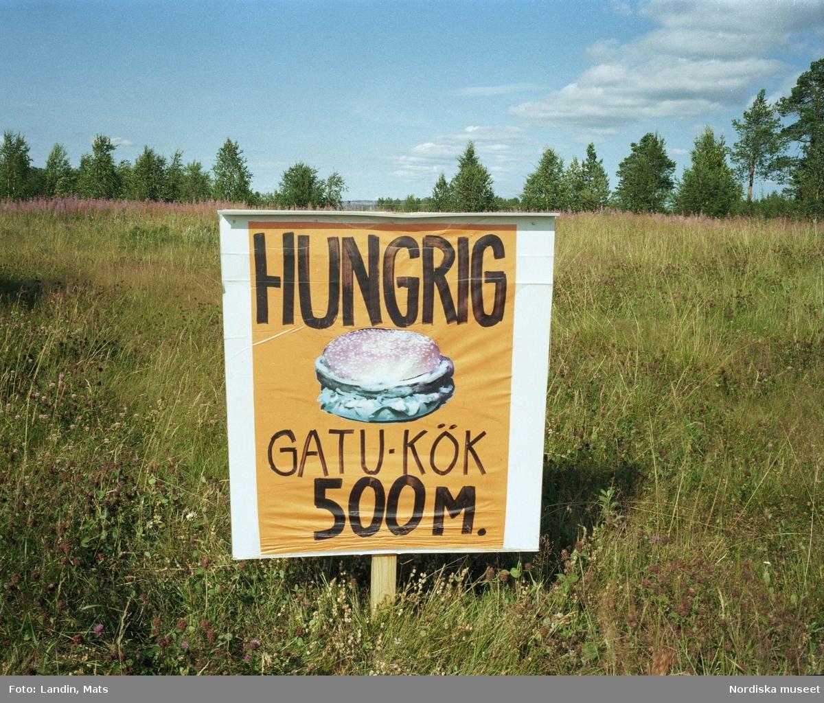 """Reklamskylt för hamburgare med texten: """"Hungrig – Gatu-kök 500 m."""" Vilhelmina."""