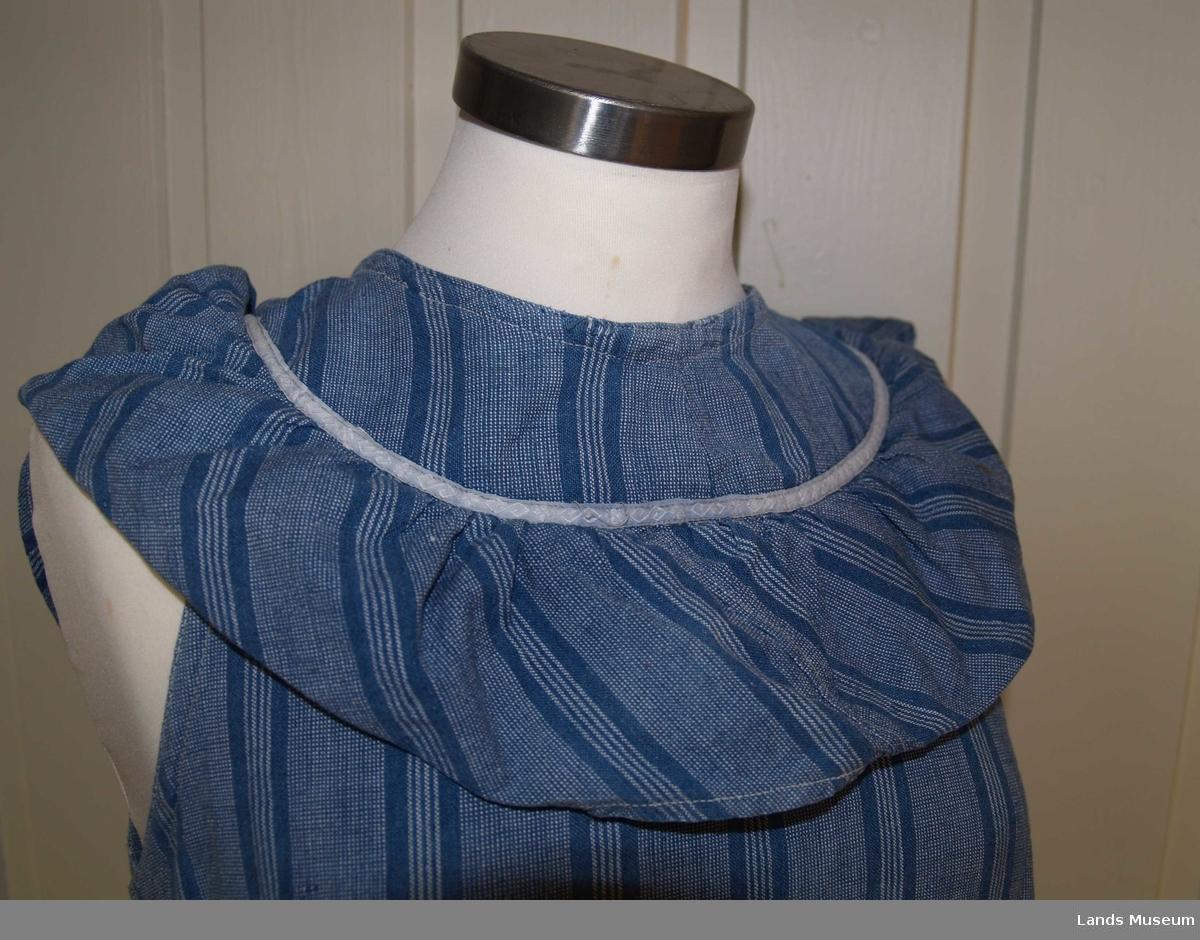 Heldekkende forkle i bomull uten ermer. Det er laget av et blågrått stoff med landsgående striper i en mørkere blå farge. Rundt halsen har det en påsydd rynket kappe i samme stoff, stoffet er skråstilt, det samme sees nederst på forkleet. Forkleet har en lomme på forsiden og åpning bak som kan lukkes med tre lerretsknapper. det er påsydd et kvitt pyntebånd over begge skråkappene og rundt lommen. På forsiden er en rift som det er bøtet på. På forkleets venstre side er et knytebånd i samme stoff som forkleet, dette mangler på høyre side.