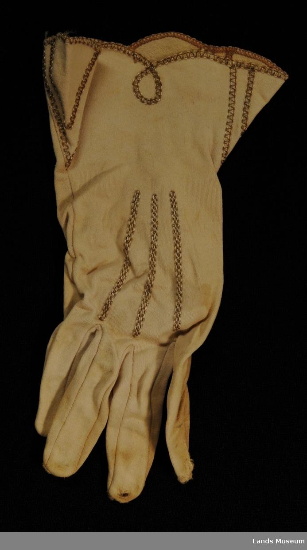"""En hanske, kort med broderte stiklinger på oversiden. Brodert løkkekant ved håndleddet. Vide ved åpning, """"klokkeformet"""""""