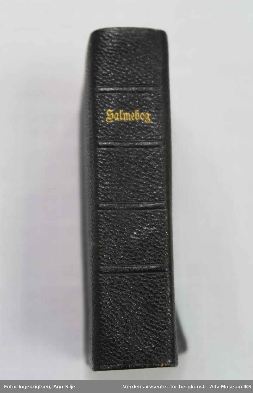 Sort liten salmebok med skinnpermer.