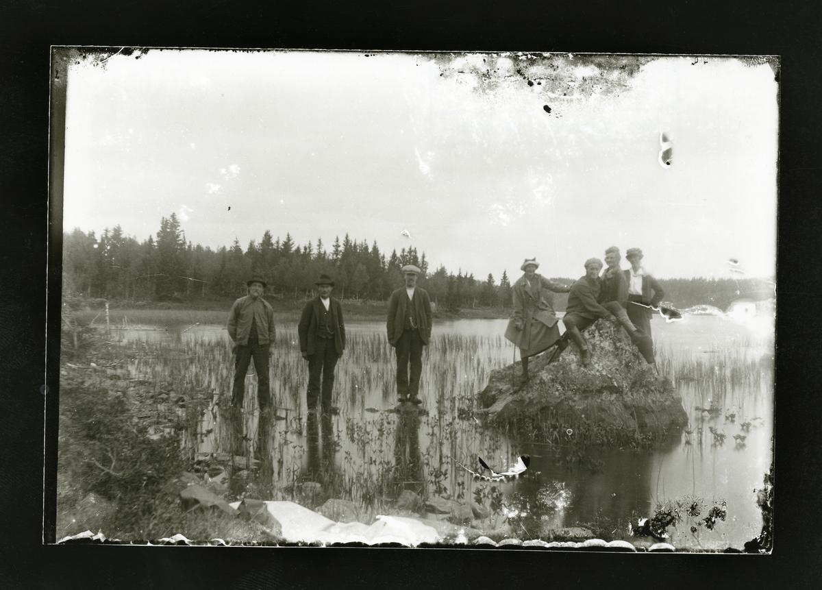 Islagt vann. 3 menn står på isenog 3 kvinner og en mann har klatret opp på en stein med is rundt.