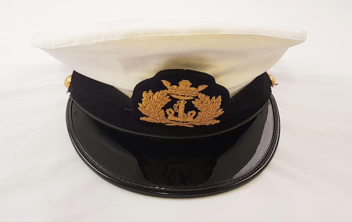 Norsk kapteinsuniformuniform bestående av bukse, jakke og lue i marineblått ullstoff. Jakken har tre gullstiper og diamant, noe som tilsier at dette er en kapteinsuniform.