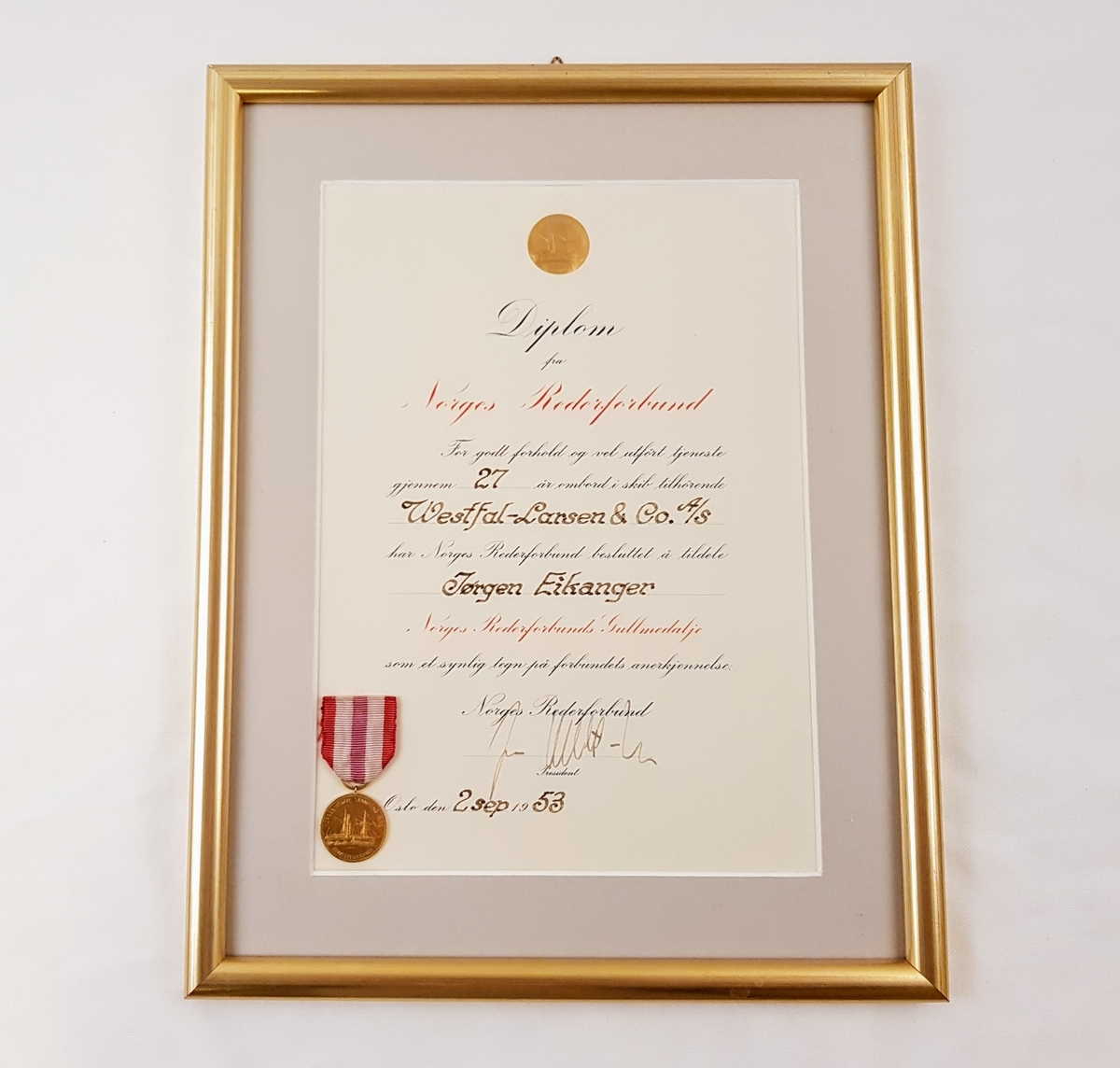 Diplom og gullmedalje i ramme med glass.