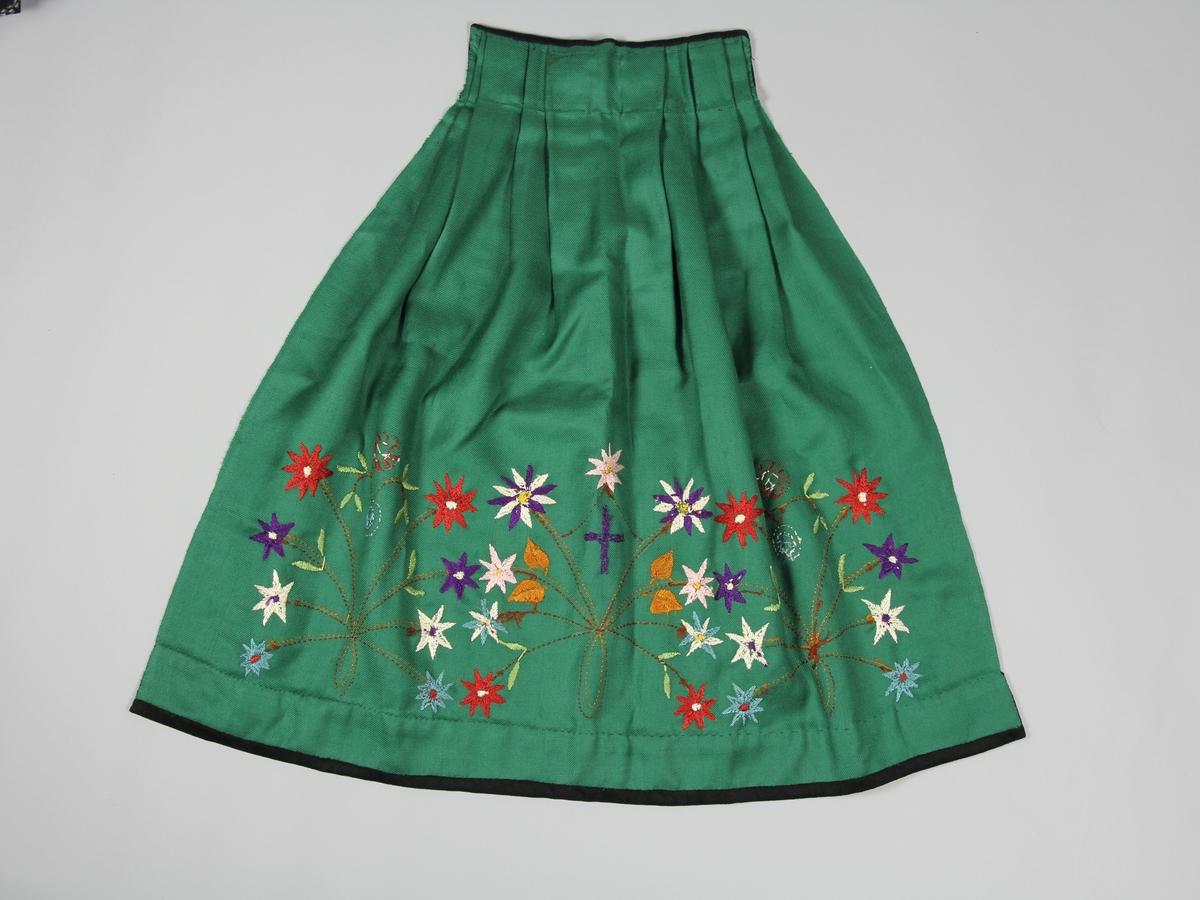Förkläde för flicka av grön ullkypert. Hör till Vingåkersdräkt för ungmö.  Rynkad mot midjan. Vid midjan och nedre kanten är det påsytt en svart bård med broderier. I förklädets nederkant är blommor och slingor borderade. Förklädet saknar knytband.