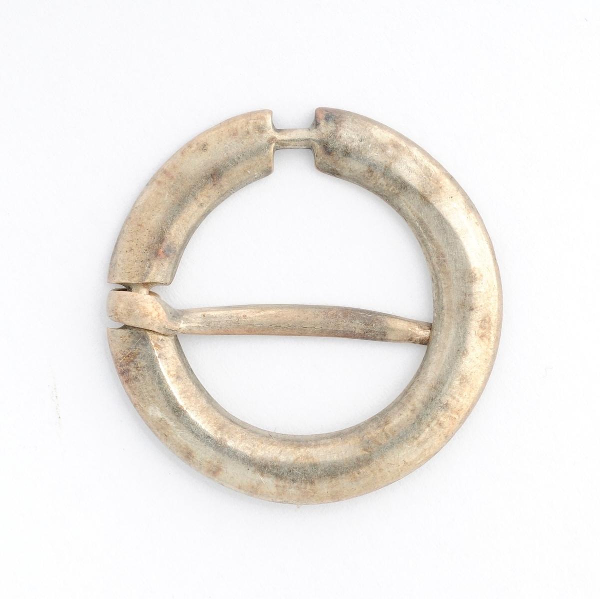 Sølje, halsring i sølv (utan stempel). Sirkulær med avrunda  framside.  To nåler, den eine manglar. Glatt på båe sider, men innrissa BSD på baksida.