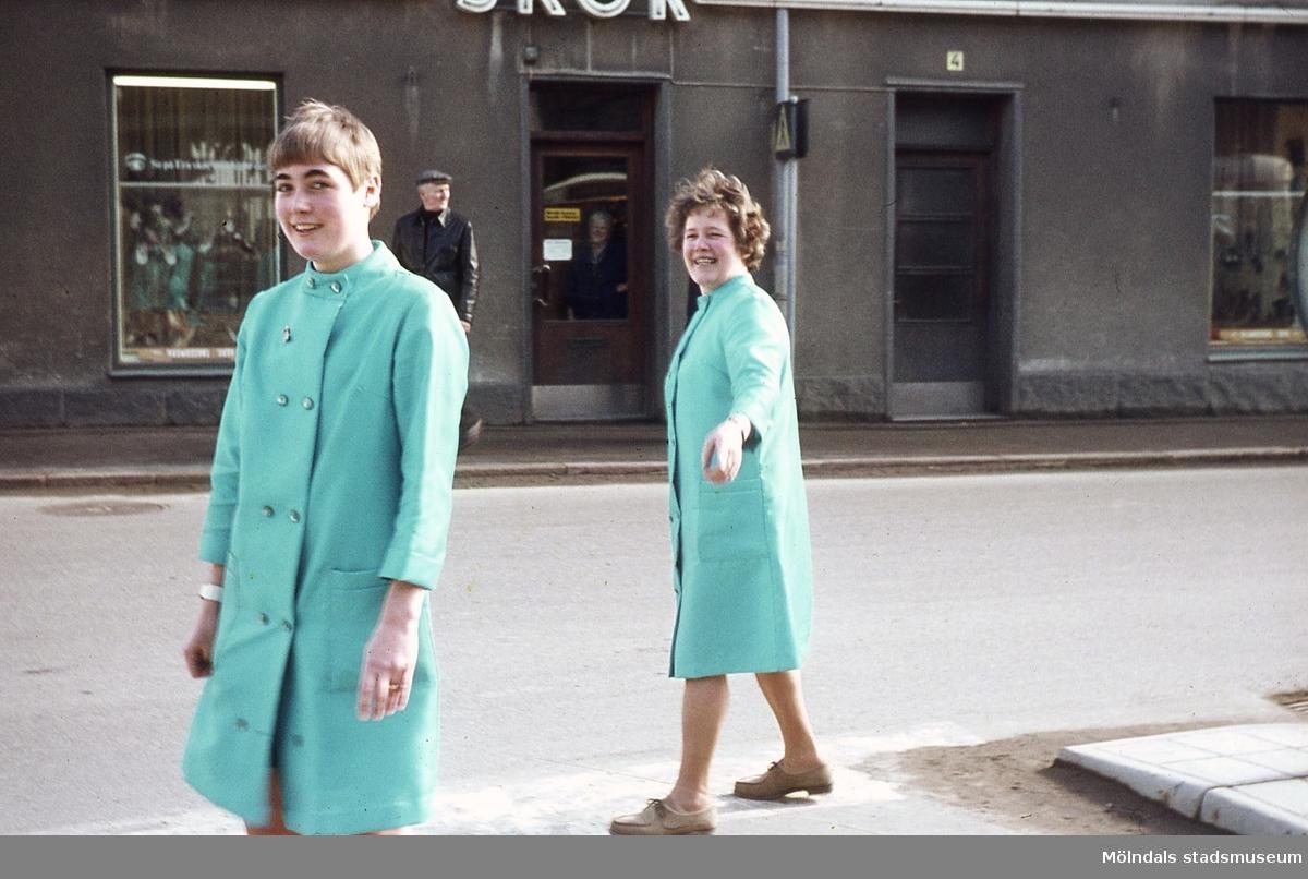 Två kvinnor och en man utanför Leon Rasmussons skoaffär på Kvarnbygatan 4 vid Gamla torget i Mölndal, 1970-tal. Kvinnan till vänster hette troligen Katie och var biträde i skoaffären. Kvinnan till höger är Märta Sjöberg, som var hembiträde hos Tant Karin, d.v.s. Karin Gren, som skymtas bakom affärens entrédörr. Karin var ägare av skoaffären där Märta periodvis hjälpte till. Kv 45:6.